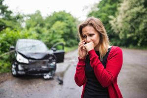 A frustrated young woman with smartphone by the damaged car after a car accident, making a phone call.